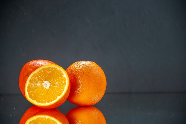 Vooraanzicht van hele gesneden verse sinaasappelen die naast elkaar staan op licht op zwarte achtergrond met vrije ruimte