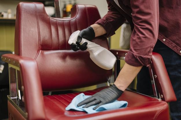 Vooraanzicht van herenkapper die de stoel schoonmaakt
