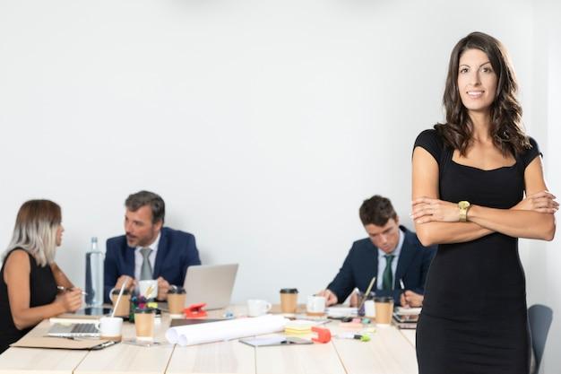 Vooraanzicht van het bedrijfsvrouw stellen in bureau