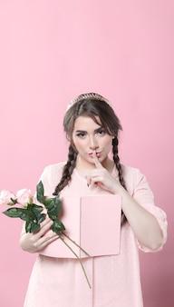 Vooraanzicht van het boek en de rozen van de vrouwenholding en het zetten van vinger over mond