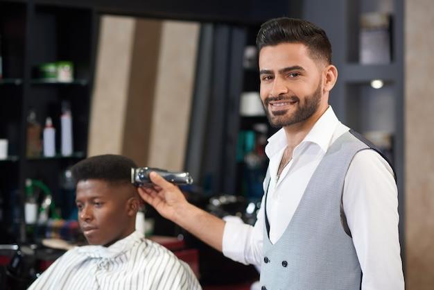 Vooraanzicht van het gekwalificeerde kapper stellen in kapperswinkel