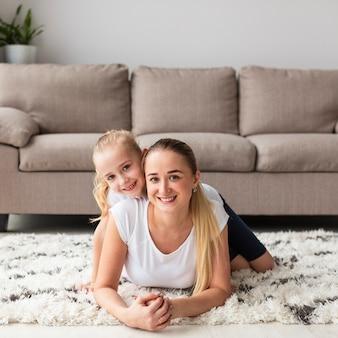 Vooraanzicht van het gelukkige moeder en dochter stellen thuis