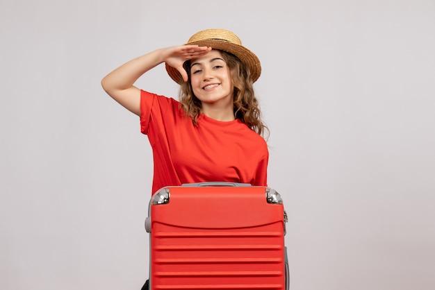 Vooraanzicht van het gelukkige vakantiemeisje met haar valise status op witte muur