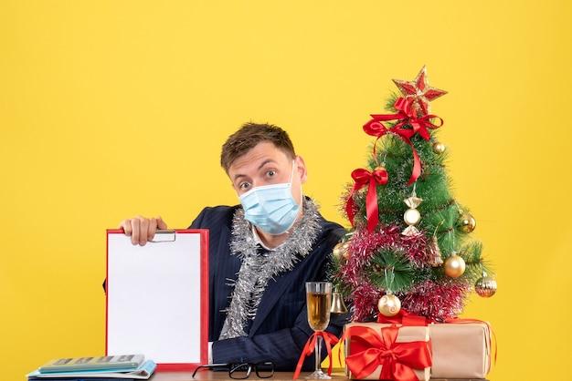 Vooraanzicht van het klembord van de bedrijfsmensenholding aan de tafel dichtbij de kerstboom en stelt op geel voor