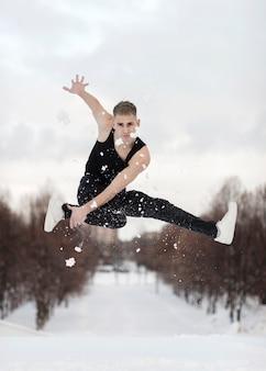 Vooraanzicht van het mannelijke hiphopuitvoerder stellen in mid-air met sneeuw