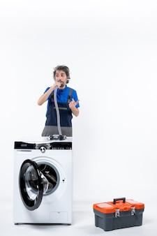 Vooraanzicht van het observeren van de reparateur in uniform staande achter de wasmachine die de pijp op de witte muur blaast
