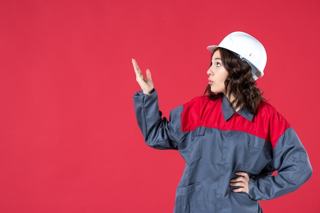 Vooraanzicht van het ondervragen van vrouwelijke bouwer in uniform met harde hoed en omhoog wijzend op geïsoleerde rode achtergrond