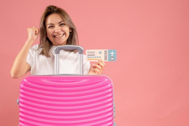 Vooraanzicht van het opgewekte kaartje van de jonge vrouwenholding achter roze koffer