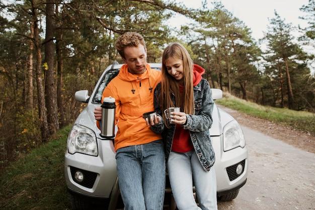 Vooraanzicht van het paar samen op een roadtrip die van warme drank geniet