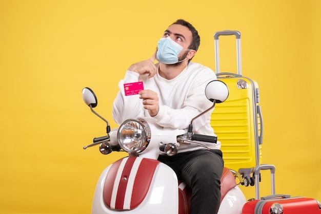 Vooraanzicht van het reisconcept met een jonge denkende man met een medisch masker die op een motorfiets zit met een gele koffer erop en een bankkaart vasthoudt
