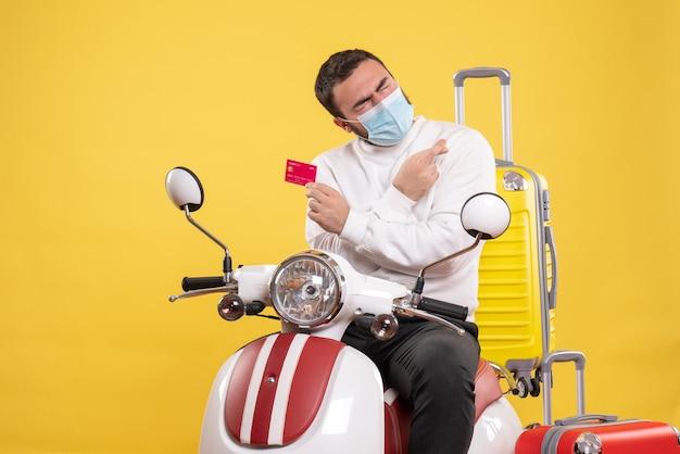 Vooraanzicht van het reisconcept met een jonge hoopvolle man met een medisch masker die op een motorfiets zit met een gele koffer erop en een bankkaart vasthoudt