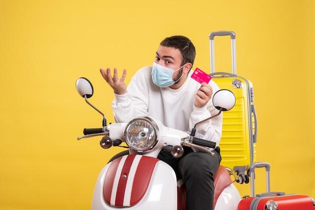 Vooraanzicht van het reisconcept met een jonge kerel met een medisch masker die op een motorfiets zit met een gele koffer erop en een bankkaart vasthoudt