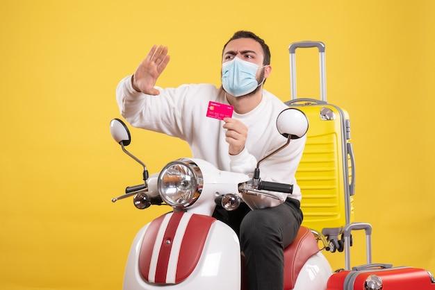 Vooraanzicht van het reisconcept met een jonge nerveuze man met een medisch masker die op een motorfiets zit met een gele koffer erop en een bankkaart vasthoudt