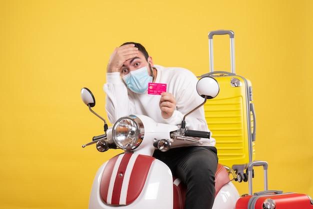 Vooraanzicht van het reisconcept met een jonge uitgeputte man met een medisch masker die op een motorfiets zit met een gele koffer erop en een bankkaart vasthoudt