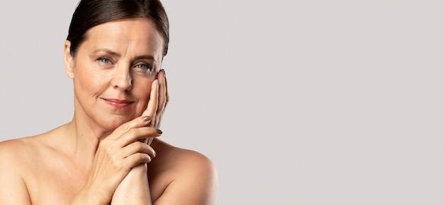 Vooraanzicht van het rijpe vrouw stellen met make-up en kopieer de ruimte