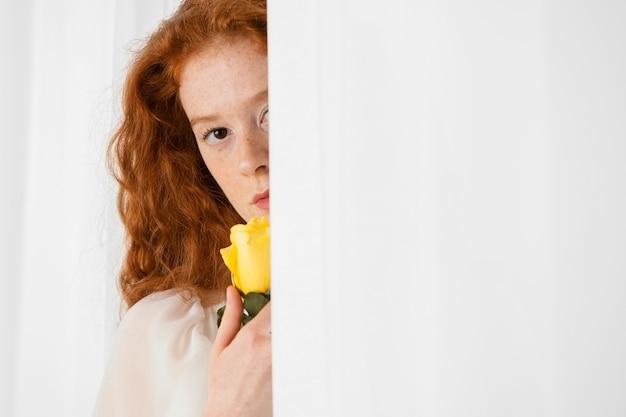 Vooraanzicht van het verleidelijke vrouw stellen met een de lentebloem en exemplaarruimte