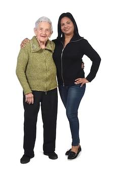 Vooraanzicht van het volledige portret van de zuid-amerikaanse vrouw die zorgt voor een oude vrouw,