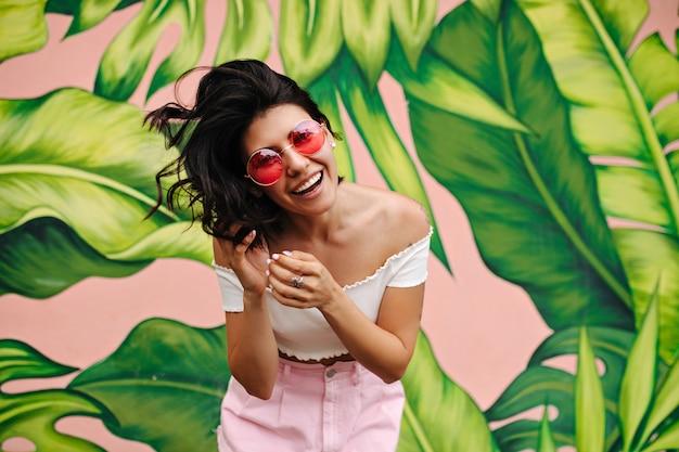 Vooraanzicht van het vrolijke donkerbruine vrouw stellen naast groene graffiti Gratis Foto