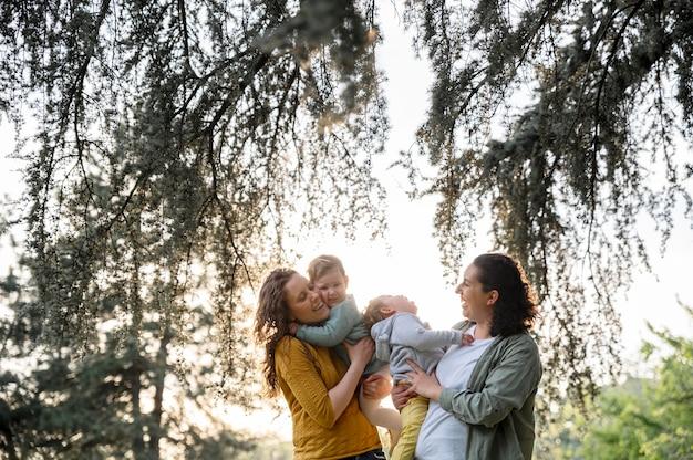 Vooraanzicht van holebi-moeders buiten in het park met hun kinderen