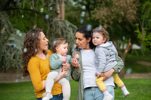 Vooraanzicht van holebi-paar buitenshuis met kinderen en zeepbellen