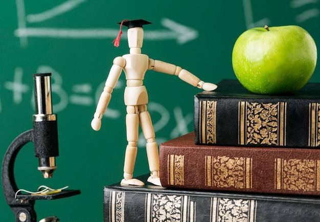 Vooraanzicht van houten beeldje met academische pet en appel