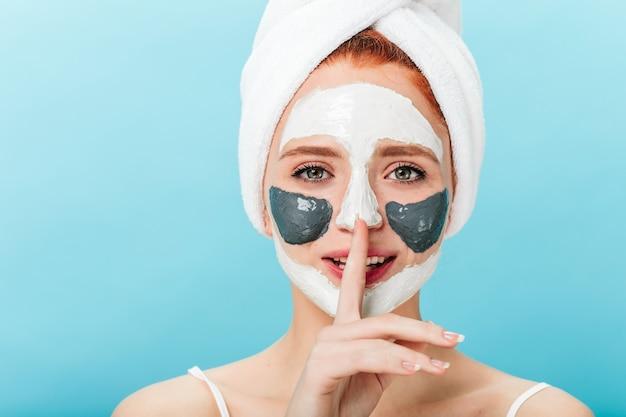 Vooraanzicht van huiveringwekkende dame met gezichtsmasker dat stilte teken toont. studio shot van ontspannen vrouwelijk model met handdoek op hoofd geïsoleerd op blauwe achtergrond.