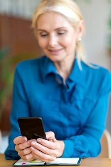 Vooraanzicht van intreepupil vrouw met smartphone tijdens het werken