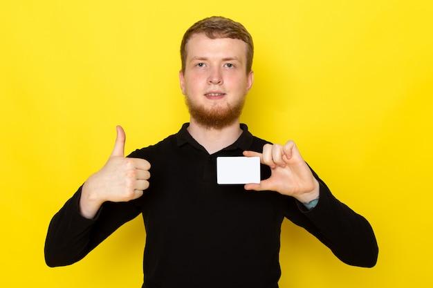 Vooraanzicht van jong mannetje dat in zwart overhemd witte kaart houdt