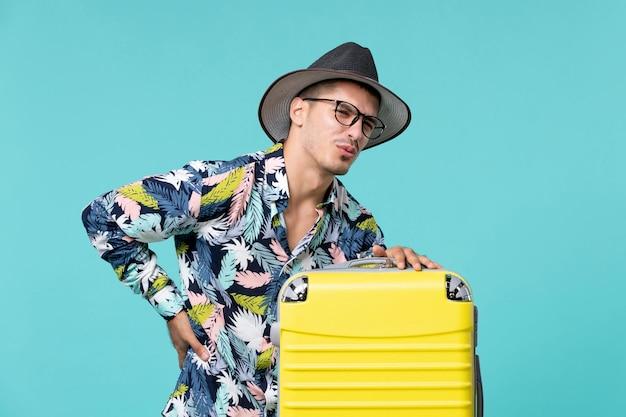 Vooraanzicht van jong mannetje dat met zijn gele zak reis voorbereidt en rugpijn op blauwe muur heeft