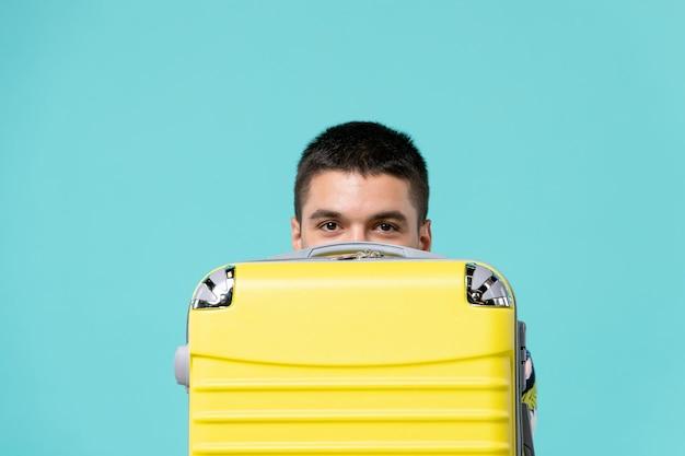 Vooraanzicht van jong mannetje dat voor vakantie met gele zak voorbereidingen treft die erachter op blauwe muur verbergen
