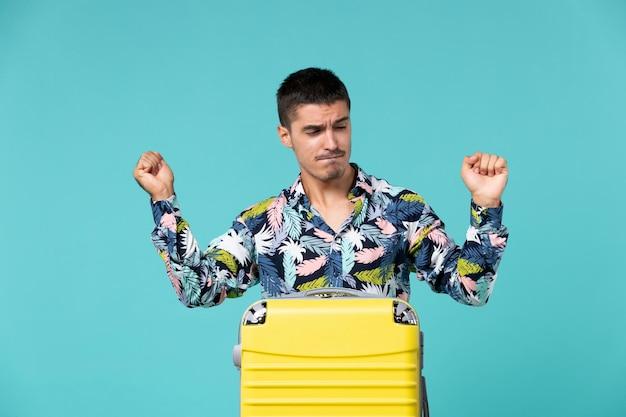 Vooraanzicht van jong mannetje dat voor vakantie met zak voorbereidingen treft die op blauwe muur proberen te dansen