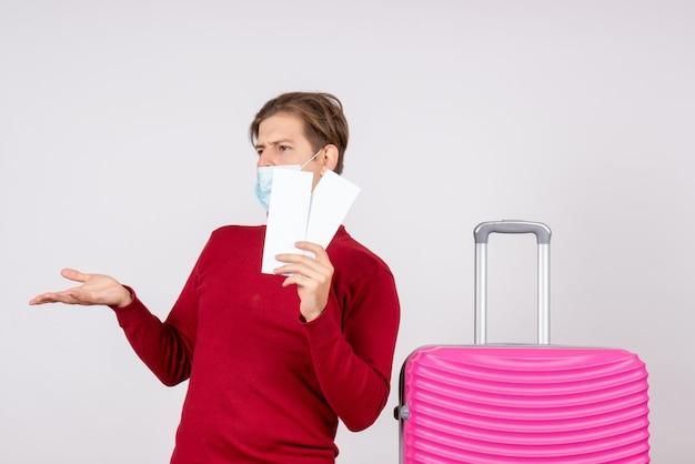 Vooraanzicht van jong mannetje in de vliegtuigkaartjes van de maskerholding op de witte muur