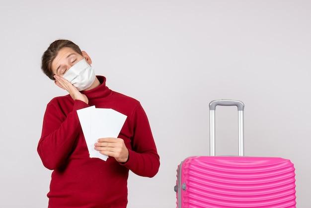 Vooraanzicht van jong mannetje in de vliegtuigkaartjes van de maskerholding op de witte muur Gratis Foto