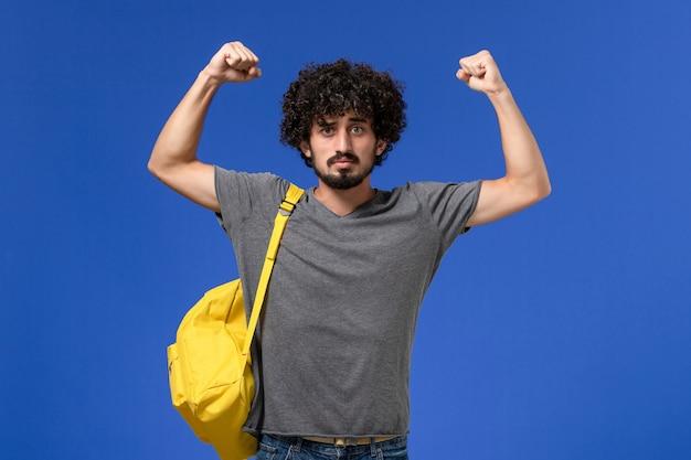 Vooraanzicht van jong mannetje in grijs t-shirt die gele rugzak draagt die op de blauwe muur buigt