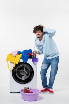 Vooraanzicht van jong mannetje met wasmachine die vloeibaar poeder op witte muur houdt