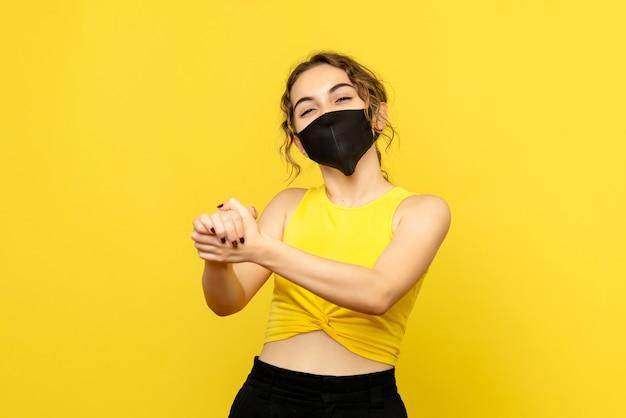 Vooraanzicht van jong meisje met opgetogen gezicht op gele muur