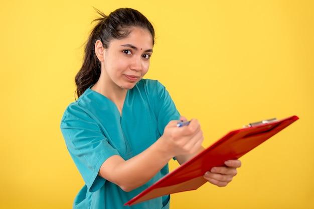 Vooraanzicht van jong vrouwelijk holdingsklembord dat pen op gele muur geeft