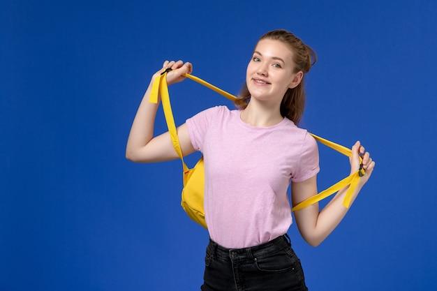 Vooraanzicht van jong wijfje dat in roze t-shirt gele rugzak houdt die enkel op blauwe muur glimlacht