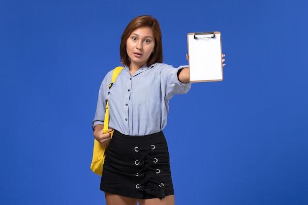 Vooraanzicht van jong wijfje in blauw overhemds zwarte rok die gele rugzak draagt en blocnote op de blauwe muur houdt