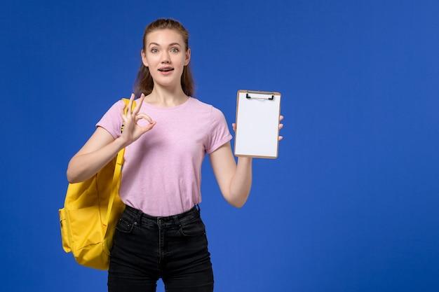 Vooraanzicht van jong wijfje in roze t-shirt die gele rugzak draagt en blocnote houdt die op blauwe muur stelt
