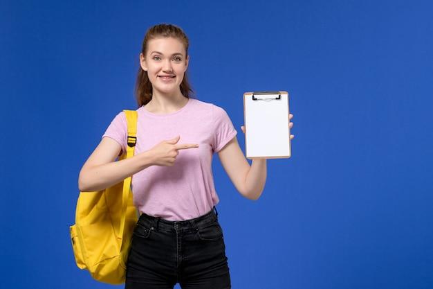 Vooraanzicht van jong wijfje in roze t-shirt die gele rugzak draagt en blocnote houdt die op de blauwe muur glimlacht