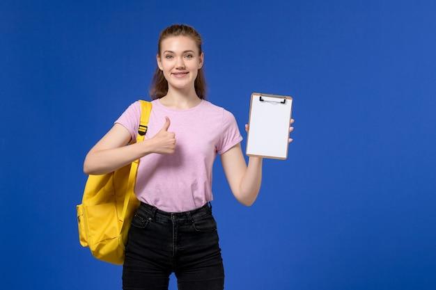 Vooraanzicht van jong wijfje in roze t-shirt die gele rugzak draagt en blocnote met glimlach op blauwe muur houdt