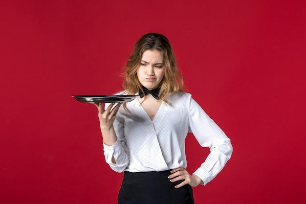 Vooraanzicht van jonge bezorgde vrouwelijke servervlinder op de nek en dienblad op rode achtergrond te houden