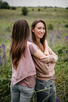 Vooraanzicht van jonge brunette meisjes die in het veld staan met hoog groen gras en lupines en glimlachen