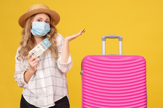 Vooraanzicht van jonge dame die masker draagt dat kaartje toont en zich dichtbij haar roze zak afvraagt