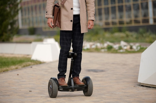 Vooraanzicht van jonge eigentijdse elegante man met leerzak die zich op gyroscoop bevindt en naar het zakencentrum in de ochtend verhuist