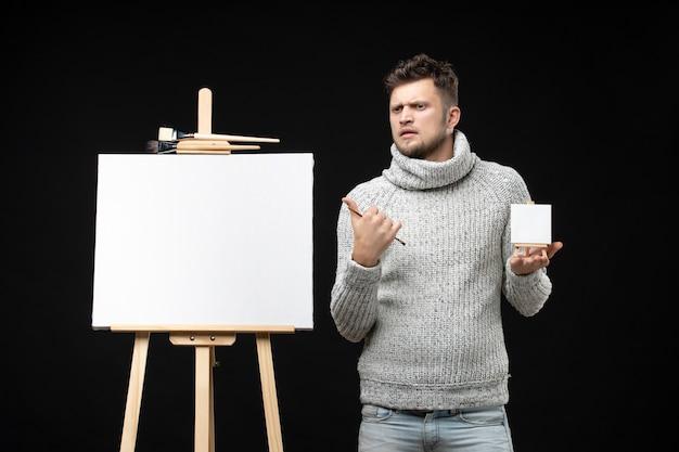 Vooraanzicht van jonge en getalenteerde, onzekere, onzekere mannelijke artiest die een mini-boek met borstel vasthoudt met een verbaasde gezichtsuitdrukking op zwart