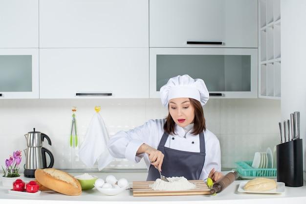 Vooraanzicht van jonge geconcentreerde vrouwelijke chef-kok in uniform voedsel bereiden in de witte keuken