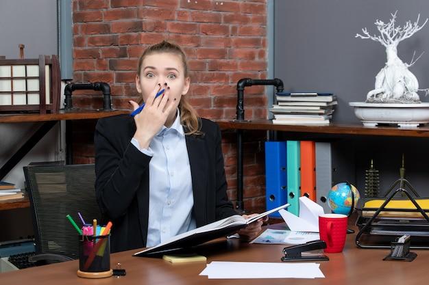 Vooraanzicht van jonge geschokte vrouwelijke assistent die aan haar bureau zit en document op kantoor vasthoudt
