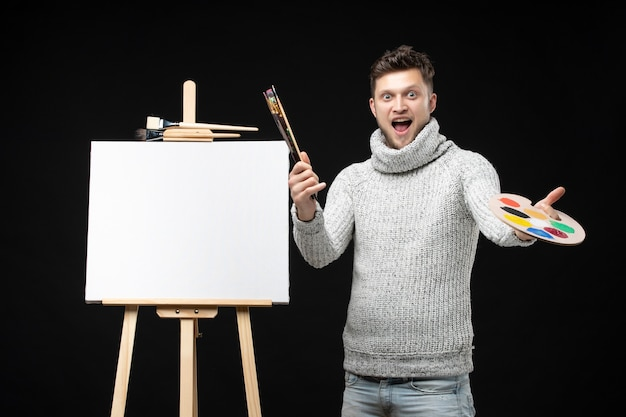 Vooraanzicht van jonge getalenteerde grappige emotionele mannelijke schilder die olieverfschilderij in gemengde kleuren op palet op zwart toont
